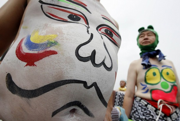 A drawing of a face is seen on a man's stomach during Bellybutton Festival in Shibukawa
