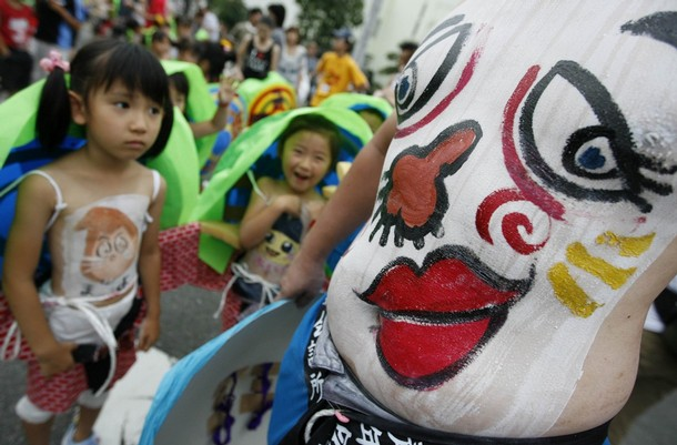 Girls look at a man's stomach with a drawing of a face during Bellybutton Festival in Shibukawa