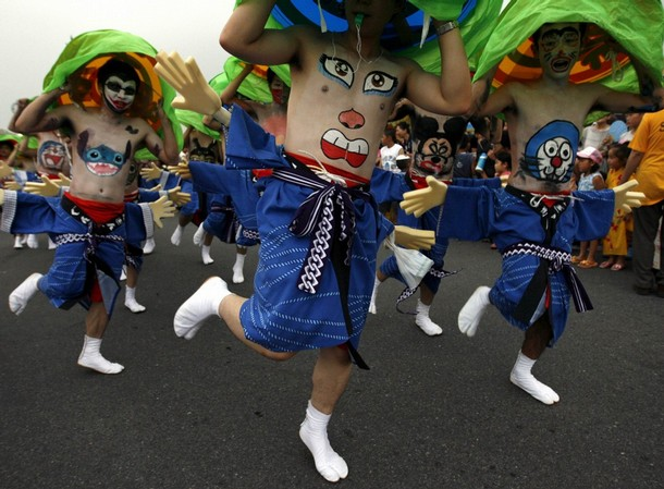 Participants with drawings of faces on their stomachs dance during Bellybutton Festival in Shibukawa
