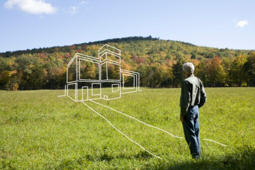 Man standing in field admiring imaginary house